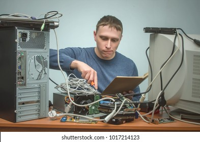 Computer technician holding in hands a manual book and is installing a new computer components. PC repair service center.
