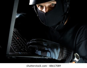 Computer theft on laptop at night, internet crime online