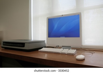 computer turned on, located next to scanner - perfect for business or school use