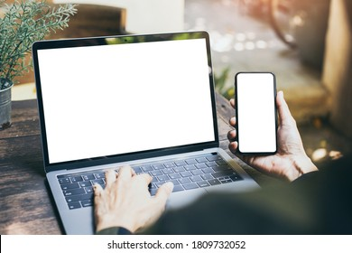 computer,cell phone mockup.hand woman work using laptop texting mobile.blank screen with white background for advertising,contact business search information on desk in cafe.marketing,design
