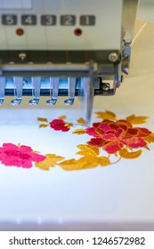 Computerized embroidery machines. sewing machine on blurred background. textile workshop. closeup. vertical photo