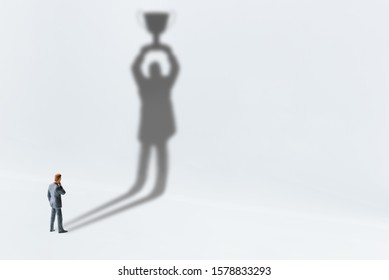 Comtemplating on business success, top performance, winner concept : Businessman looks his shadow raising a trophy cup on the wall, depicts scrutinizing on ways to race and achieve goals and win prize