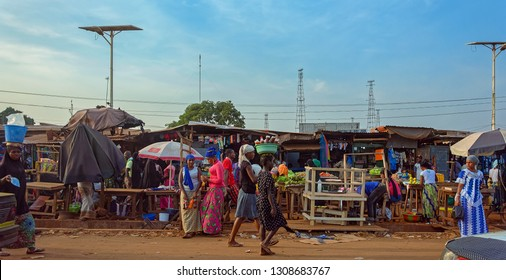 CONAKRY, GUINEA - Dec 15, 2018: Street scene with the buyers, vendors selling their goods in a street market in the outskirt of Conakry city.