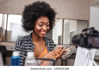 Concealer palette. Cute dark-skinned woman with coral lipstick smiling while holding concealer palette in her hand