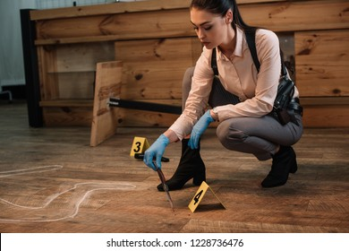 concentarted female detective collecting evidence at crime scene