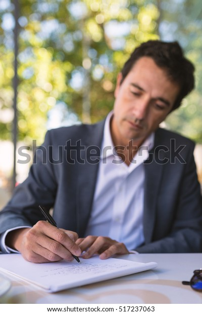 concentrate middle age businessman portrait writing stock photo  concentrate middle age businessman portrait writing an essay outdoors in  rome italy focus on