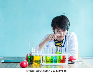 Concentrate young man scientist holding tube and looking at it while sitting at laboratory with white background. Discovering cure.  Students working at the laboratory classroom.
