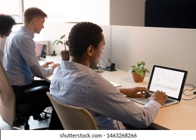 Concentrated african American employee sit work at laptop in coworking space analyzing company financial statistics, male black analyst busy using computer checking trade rates on stock exchange