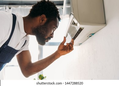 concentrated african american repairman looking at broken air conditioner