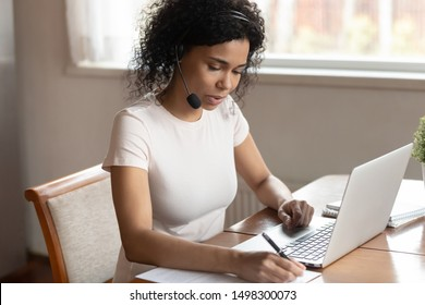 Concentrated african American woman call center agent wear headset work on laptop write consult client online, focused biracial female worker busy making notes listen watch webinar on computer
