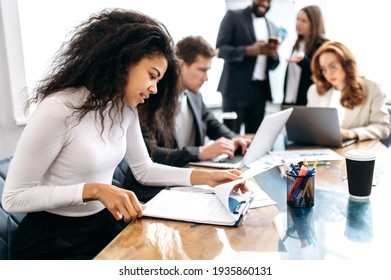 Concentrated african american woman doing paperwork, sitting in modern office on conference. Focused business lady learning financial graphs, working on corporate project at briefing meeting - Shutterstock ID 1935860131