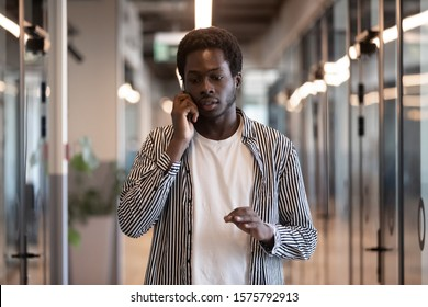Concentrated african entrepreneur walking in office hallway talking using mobile phone speak with customer doing work distantly solving issues consulting client, employee having busy fruitful workday