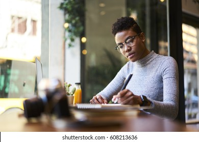 Concentrated afro american experienced woman journalist in glasses creating article working in coffee shop, skilled young female graphic designer making sketch in notebook for new startup project