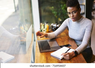 Concentrated afro american freelancer making notes of information from internet sitting in cafe interior, prosperous owner in trendy eyewear of online store writing report organising working process