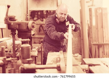 Concentrated artisan in a blue robe is shaping timber on a woodworking machine at the factory
