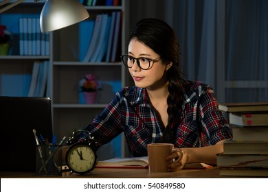 Concentrated asian young woman in glasses using computer for studying and writing in the evening at home. mixed race asian chinese model.