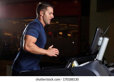 Concentrated athletic man training on a running machine in a fitness center .Low light