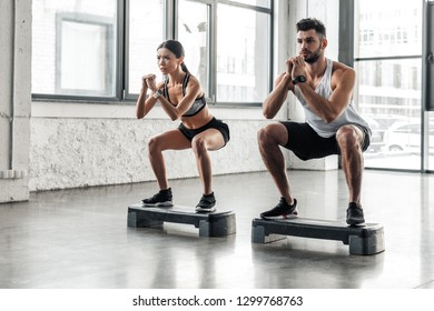 concentrated athletic young couple in sportswear squatting on step platforms in gym