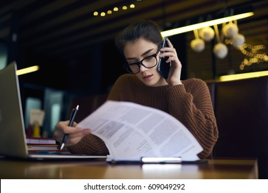 Concentrated attractive female accountant of corporation making distant work checking financial report calling to secretary discussing detail while sitting in coffee shop with laptop computer and wifi