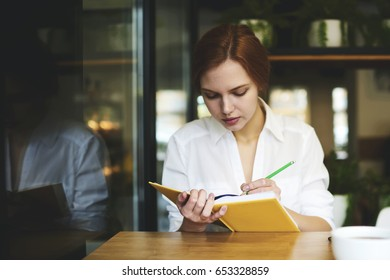 Concentrated attractive female administrative manager organising work schedule writing notes in notebook, professional journalist in formal wear handwriting article for new blog publication