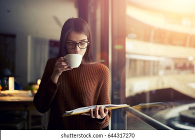 Concentrated attractive female student reading interesting literature for improving skills and knowledge,hipster girl in trendy outfit enjoying leisure time and drinking coffee during college break