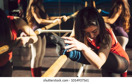 Concentrated ballet dancers training with barre in front of mirror in studio.