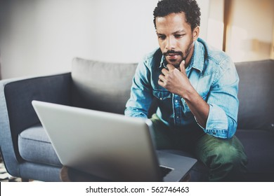 Concentrated bearded African man working at home while sitting on the sofa.Using laptop for new job search.Concept of young people using mobile devices.Blurred background