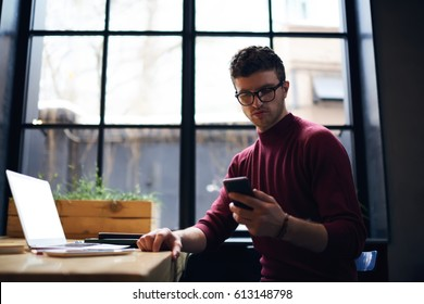 Concentrated bearded hipster guy watching streaming video via smartphone connected to 4G internet in coworking space, handsome serious male freelancer reading text messages checking email on cellular