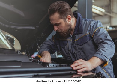 Concentrated bearded male mechanic repairing engine of an automobile. Experienced car technician servicing a car at his workshop, copy space