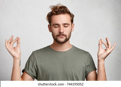 Concentrated bearded man with appealing appearance meditates against white background, tries to relax after hard working day, daydreams, keeps fingers together. Meditation and relax concept.