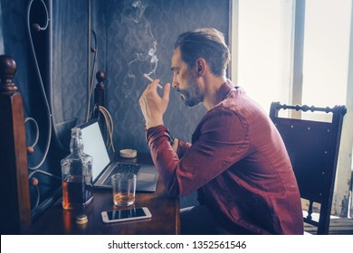 Concentrated Bearded Man Holds A Cigarette While Working On Laptop. Handsome Guy Holds A Cigarette Smoking. Bottle Of Whiskey, Smartphone And Opened Laptop Are On The Wooden Table With A Mirror. Side