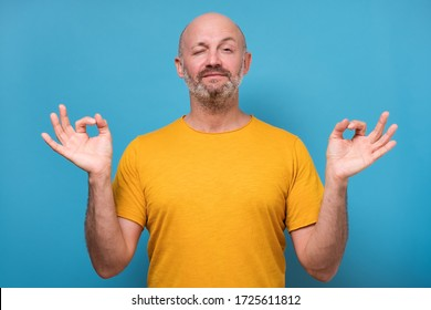 Concentrated bearded man meditates peeping opening one eye, tries to relax after hard working day, daydreams, keeps fingers together.