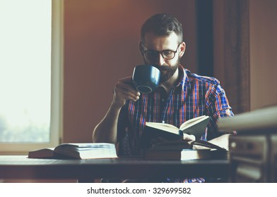 concentrated bearded man reading books and drinking coffee or tea