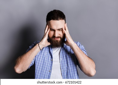 Concentrated bearded man thinking about something, holding fingers on temple, gray studio background. Brainstorm, bad memory, headache concept