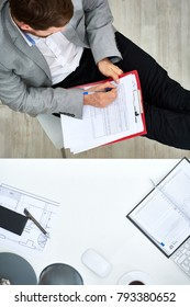 Concentrated bearded manager in formalwear sitting with legs on desk and filling in form, directly above view