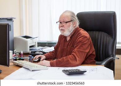 Concentrated bearded senior man using computer at desk in office room, engineer white collar worker