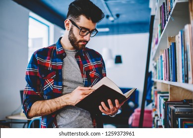 Concentrated bearded young man dressed in casual wear holding literature book in hands and searching useful information for coursework on pages standing in library near bookshelf of university