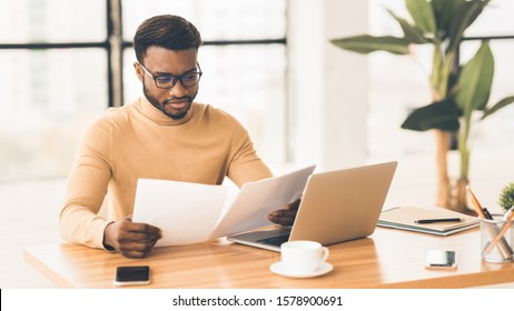 Concentrated Black Businessman Checking Financial Reports In Modern Office. Panorama, copy space