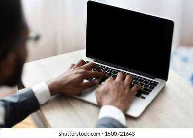 Concentrated black businessman typing on laptop with blank screen, working in office. Over shoulder shot