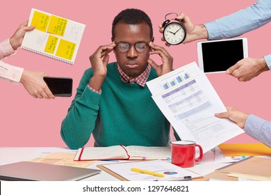 Concentrated black man keeps hands on temples, wears spectacles, green jumper, surrounded with papers, has alarm clock, touchpad, mobile phone near, thinks about much affairs, being busy all day