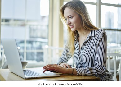 Concentrated blonde female copywriter working on creative task watching webinar for improving skills and knowledge,attractive journalist monitoring latest news on websites using laptop computer