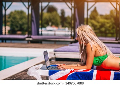Concentrated Blondie Young Woman Is Laying On The Deck Chair And Typing On Her Laptop Near The Pool.Green Bikini.Blue Water.