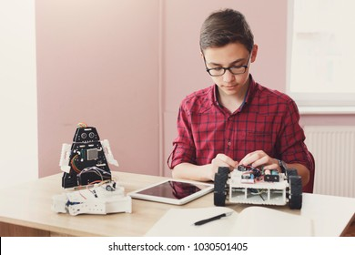 Concentrated boy creating robot at lab. Early development, diy, innovation, modern technology concept. Stem education.