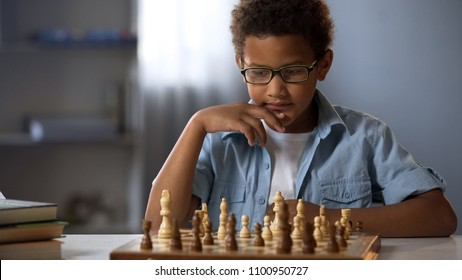 Concentrated boy developing chess strategy, playing board game with friend