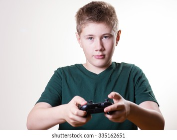 concentrated boy with gamepad. teenager holding video game controller and playing