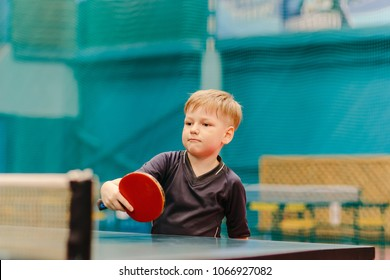 concentrated boy playing table tennis in the tennis hall