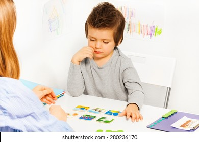 Concentrated boy plays developing game at  table
