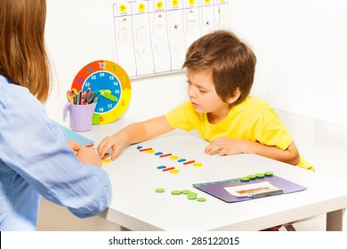 Concentrated boy puts colorful coins during ABA