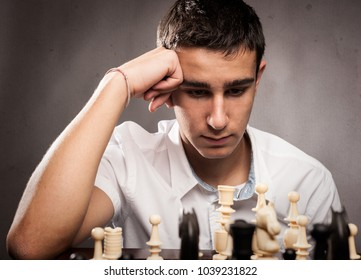 concentrated boyplaying chess on a gray background