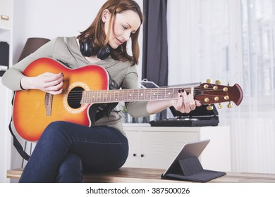 Concentrated brown haired girl with headphones around her neck playing some records on guitar while using a tablet